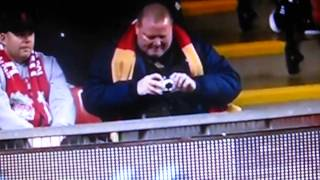 Liverpool fan takes a picture Agbonlahor after his disastrous fall in tribune