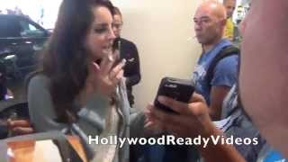 Lana Del Rey enjoys a cigarette while waiting for her car to pick her up at LAX airport in LA