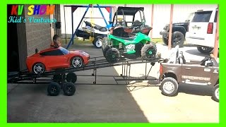 playing with his custom two car trailer loading and unloading his power wheels corvette and atv