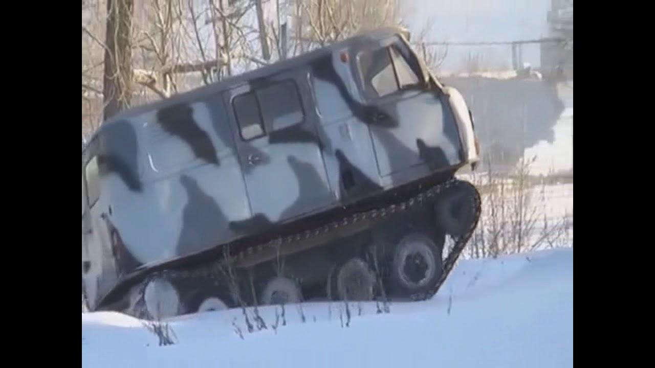 Уаз на гусеницах едет по дороге, по снежному полю и погрузка в кузов Камаза