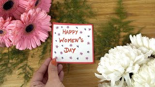 Decorated wooden table with a colorful card and flowers - International Women's Day