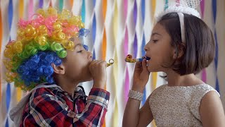 Two adorable Indian kids having fun with whistle party horns at a birthday party
