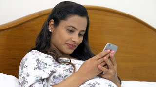 Beautiful pregnant woman texting someone on her phone while resting in the bed
