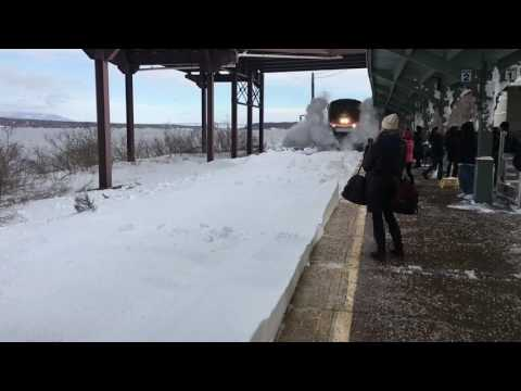 An Amtrak train roaring into Rhinebeck Station covers commuters in a shower of snow and ice blocks.
