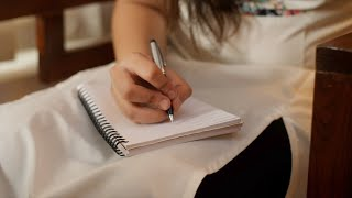Shot of a girl writing in a notebook with a pen