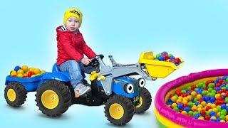 Большой синий трактор и самосвал играют в цветные шарики