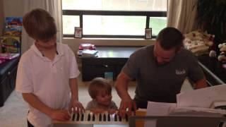 Chris Powell Family Singing Around the Piano