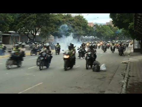 Police on motorbikes chase down protesters in Caracas