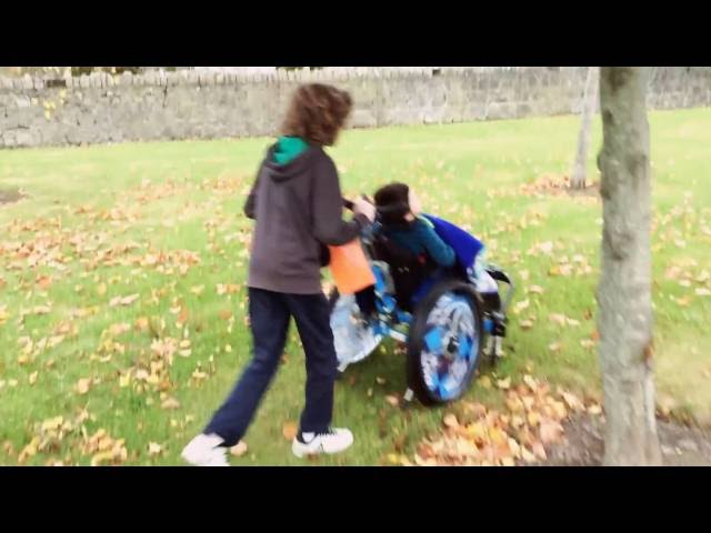 Oisin in his Veldink4kids Kiddo Tilt wheelchair with Mud Cruiser fifth wheel attachment