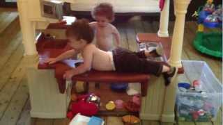Twin 20 month old cooking in kitchen