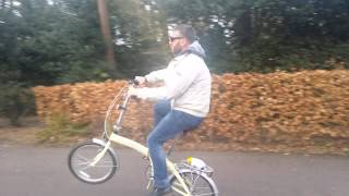 47 year old man pulling wheelies on a fold up bicycle pushbike