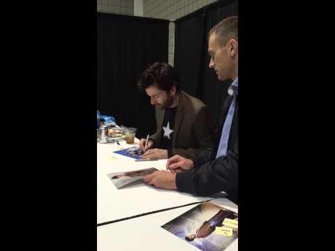 David Tennant talking to a kid while signing