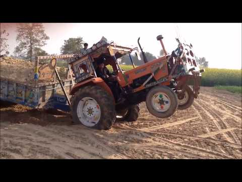 Tractor stunt with trolly pulling full loaded