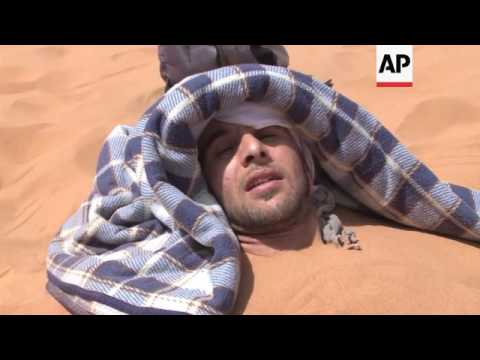 People are buried in sand dunes as alternative therapy