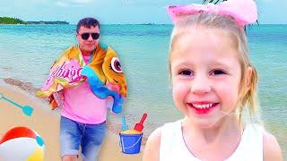 Nastya und Papa geben vor, am Strand zu spielen