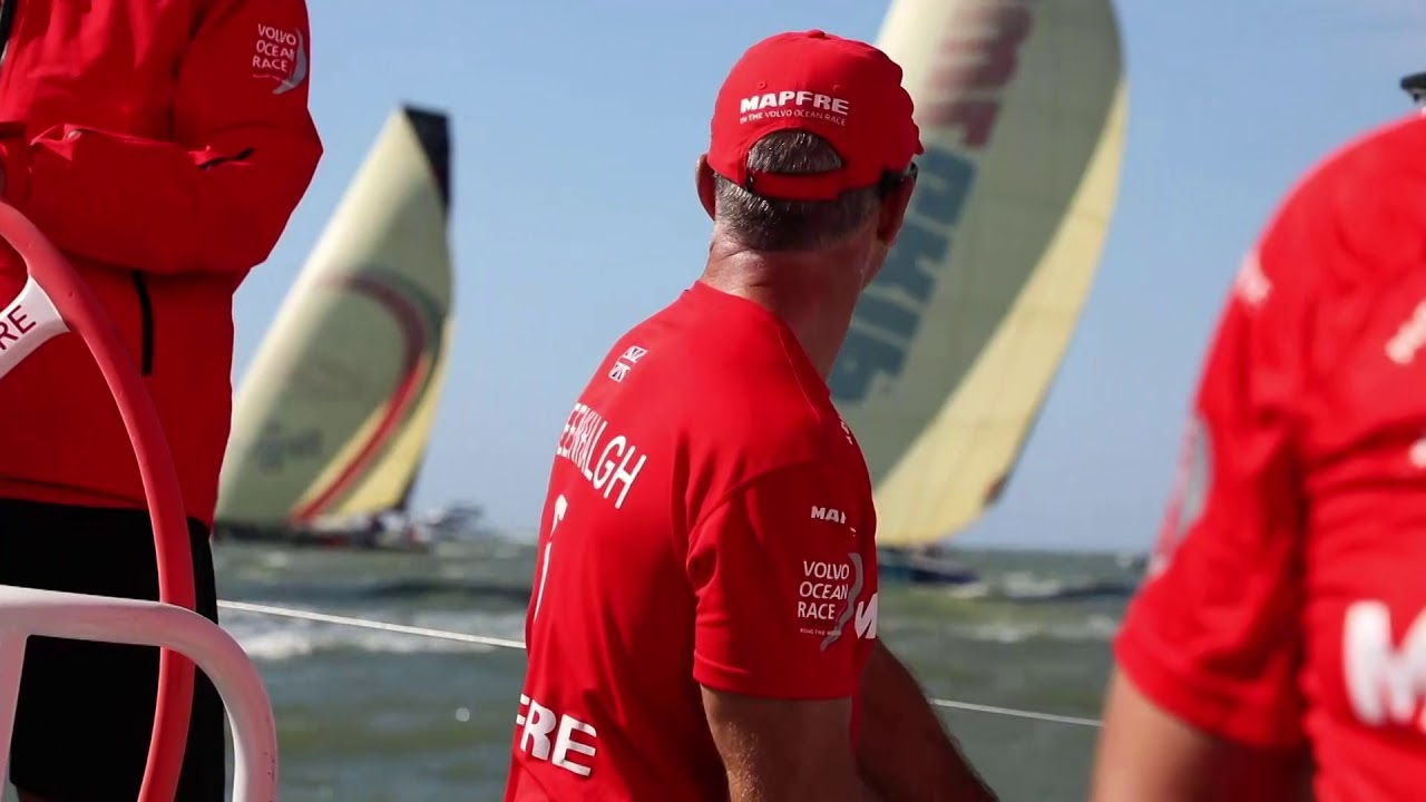 "Blair, in the prestart, talks about the upcoming leg. Rob calling tactics at the start. Brunel sailing down on them. Sailing away from the line with the best start. Neti: ""Dongfeng is tacking."" Grinding. Leading the fleet around the weather mark. Dongfeng right on their stern. Lots of cool sailhandling footage. They're doing a good job without Sophie. Neti: Start was pretty good for us... Now comes the tricky part, which is the leg. (He repeats in Spanish.) Rob recaps the start. Learned their mistakes from the in-port race. ""A long port tack now and try to stay in front."""