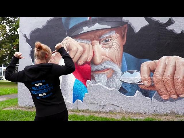 dívka v univerzitní mikině s malbou T.G.M v pozadí