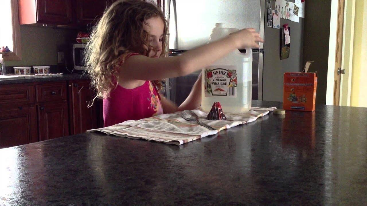 Une petite fille essaie de faire un volcan