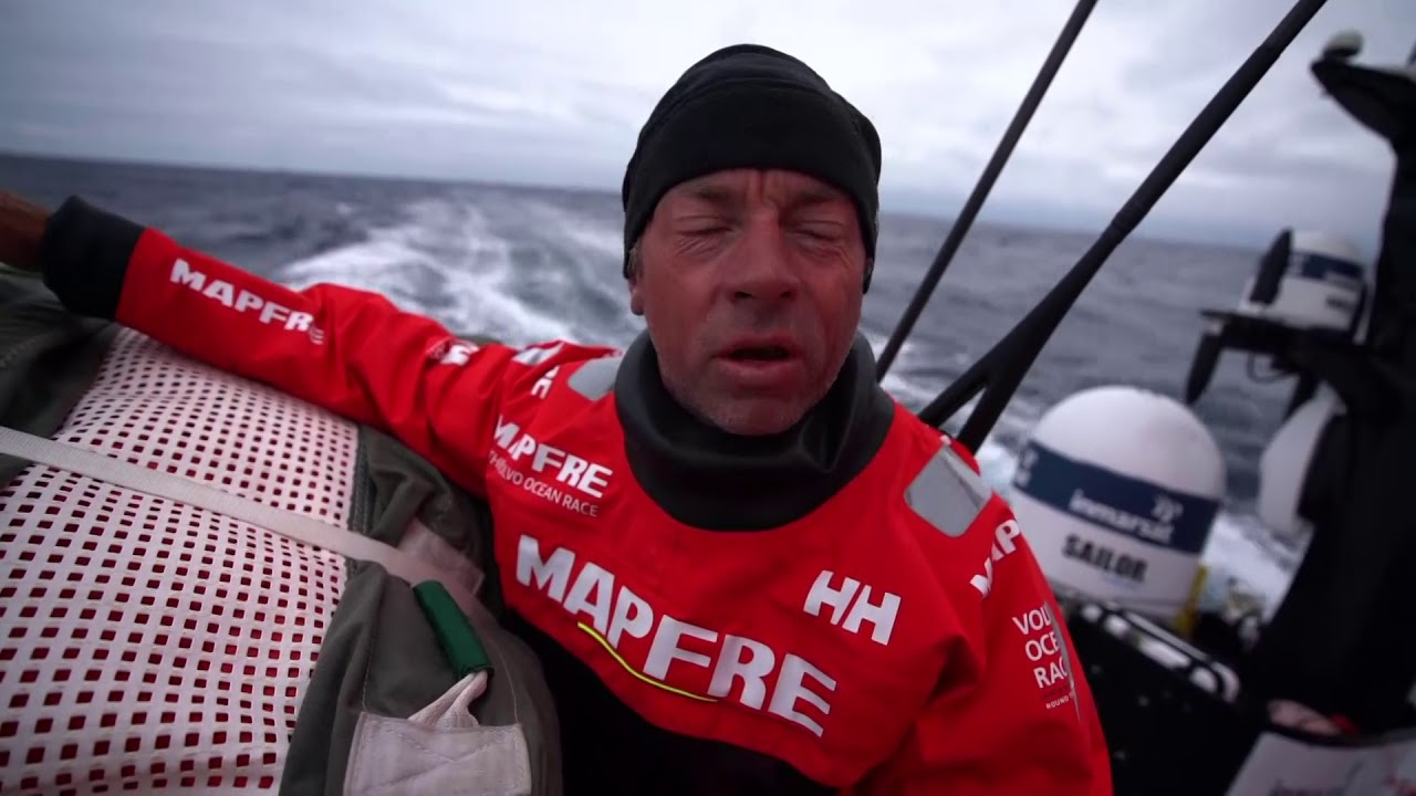 Tamara, next to the stack aft, talks in Spanish. Mentions Dongfeng, light winds, changes, waiting for strong wind. Repeats in English: Now we are in the best position. It was a tough day for the rest of the fleet. Now we have to focus on our work, doing our best. We have a lot of miles, and all the teams want to win the race. And I think we have to work hard to try to keep leading this fleet to the end of the leg. Rob: Crossing the ridge to the west of Ireland was critical. Keeping east of the fleet seems to have worked out. Made a little extension. Now we're just VMGing down toward the Hebrides. Inside or outside; could split the fleet. Neti sleeping. Xabi at the nav station talking to Joan. Pablo on the helm. Blair grinding. Rob below, getting his foulies on. Sophie and Tamara stacking below. Gybe in the cockpit. Stacking in the cockpit. Rob and Joan at the nav station. Rob: Allright; VMG then. Crew in the cockpit. Xabi looking around.