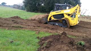 Compact track loader pushing earth