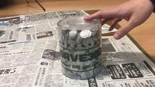 1円玉が詰まったプラスチック製の貯金箱からお金を取り出すために、貯金箱を割ります。