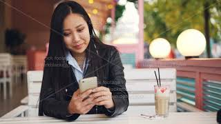 Smiling Asian girl student is resting in outdoor cafe and using smart phone touching screen and