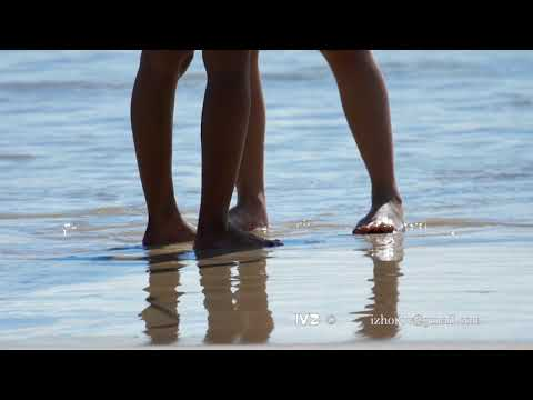 Male and female feet are standing on the sandy beach
