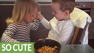 Twins preciously take turns feeding each other