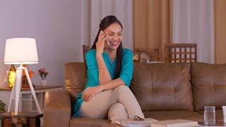 Happy Indian woman laughing while talking on the phone with friends