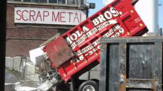 Dump Truck Dumping A Load Of Scrap Metal. Appliances, Furniture, File Cabinets and More Recycled