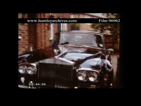 Young woman walks past Rolls Royce car.  Archive film 96962
