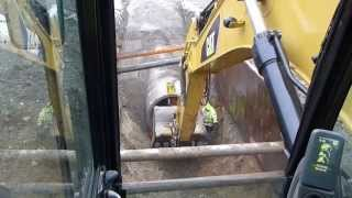 "Cat 330d digging and laying 60"" concrete drain pipe"
