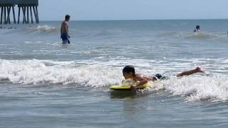 6 year old boy learning to boogie board in the ocean