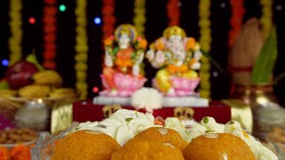 A tempting bowl of sweets for Diwali celebration with decorated blur temple in the background