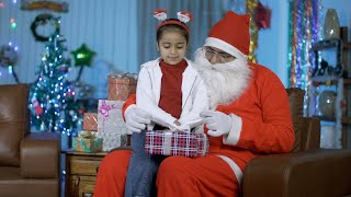 Pretty Indian girl in red hairband opening colorful gift box with Santa Claus - Christmas time