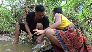 Primitive smart Girl Catch Fish in the rainy season – Survival Skills Hand Fishing and Cooking fish