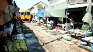 Just a passenger train passing through a busy market in Central Thailand