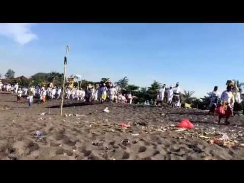Balinese villagers flood Sesah Beach for Malasti purification ceremony before Nyepi silent day.