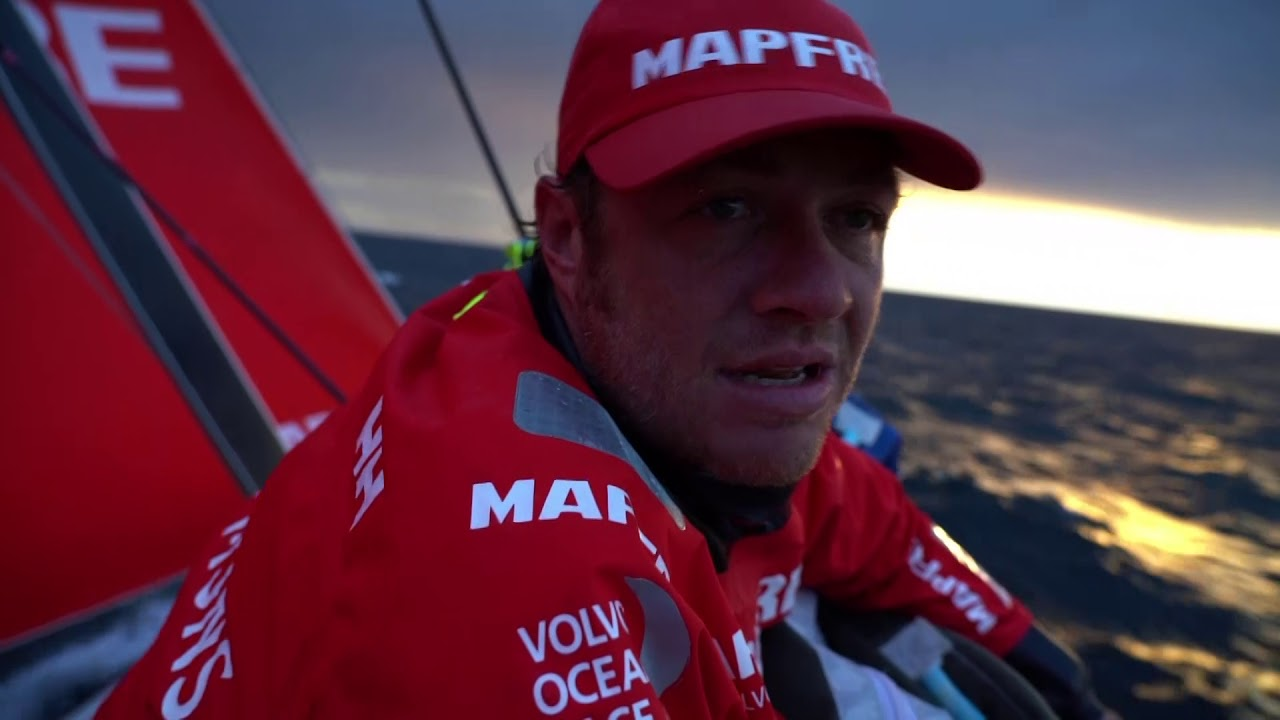 Neti, on the rail, talks in Spanish with the sunset behind him. He repeats in English: Quite a tricky afternoon. Lots of tacks, cloud, right-hand shift. Now we have Dongfeng ahead of us, and the others on our transom. So we are in the fight, and pushing. Good stuff for us. We made a mistake on the leeward layline. We took the first opportunity we have... now we have to make the less mistakes possible. Very tricky leg. We knew also with the watches that after the top mark in Norway it's going to be full on. Hopefully we can have some sleep. He interrupts to drop the J1. Other boats to weather: Brunel, AkzoNobel, and Dongfeng. Stacking. Xabi grinding. Slomo stacking. Rob: Lefthand phase still to come, and then it will build right. Is that right, Joan? Neti and Willy on the bow laughing about something. Packing a sail on the foredeck. Slomo grinding. Stacking uphill. Tack. Dongfeng ahead and to leeward.