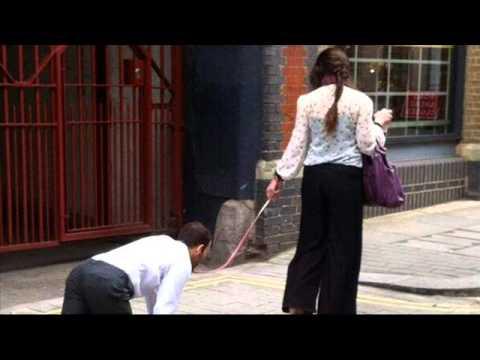 Woman walks businessman on leash in London