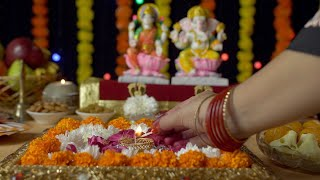 Hands of a young female praying while lighting an oil lamp in a puja Ghar at home on Diwali festival