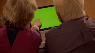Shot of an elderly Indian couple working on laptop with the green screen in their living room