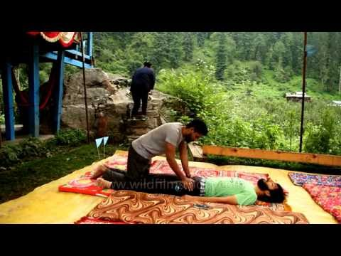 Indian therapist gives Ayurvedic massage for back pain, in the Himalaya