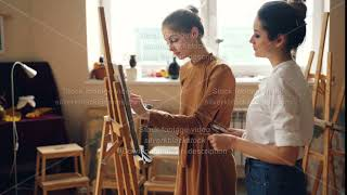 Professional teacher of art school is working with diligent girl student painting picture and