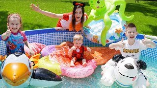 Дети покупают надувные игрушки и собираются купаться в бассейне.