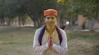 Smiling Indian guy in Kurta Pajama joining hands and greeting on Holi festival
