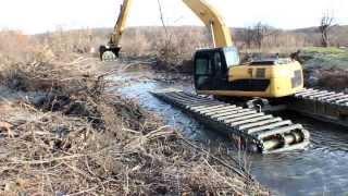 Экскаватор Амфимастер со сдвижными понтонами работает в узком канале реки