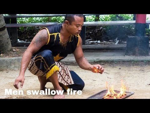 Indonesian men eating glass and swallow fire at Batam Island