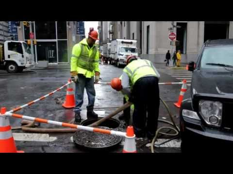 City construction workers pump the water from underground on Wall Street
