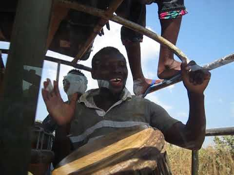 Abou Sylla playing the djembe while traveling to villages outside Conakry, Guinea